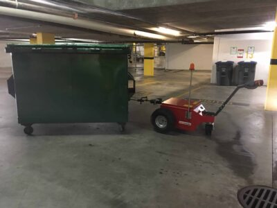 Xerowaste | V-Move XL+ AC motor heavy-duty dumpster mover tug ready to move a waste bin from an underground garage