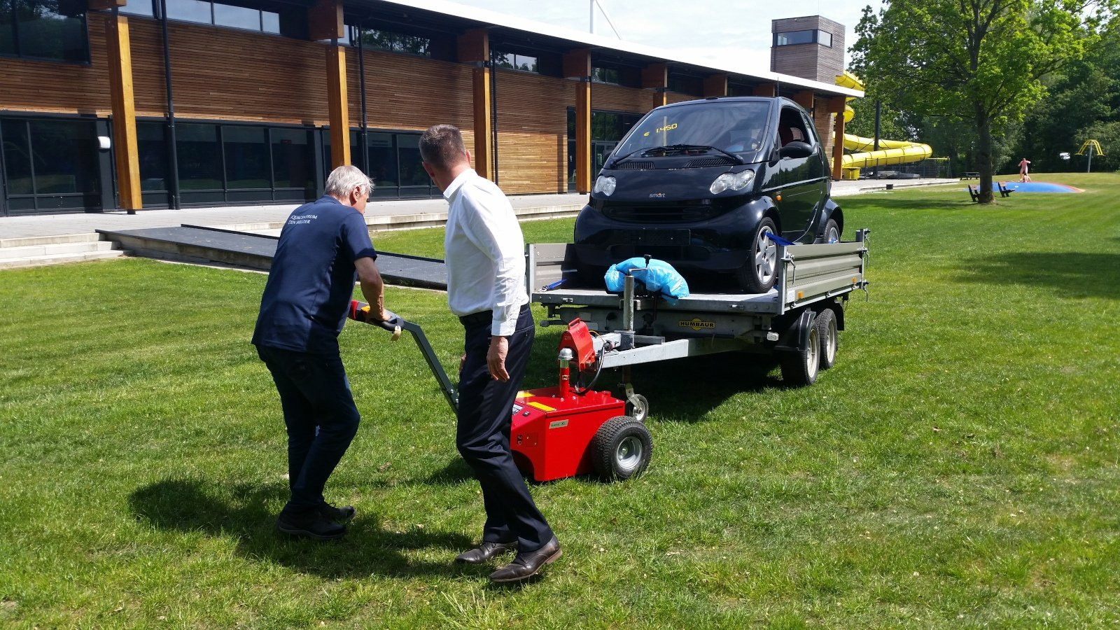 Xerowastee | V-Move XL moving trailer with a vehicle on it on a grass surface