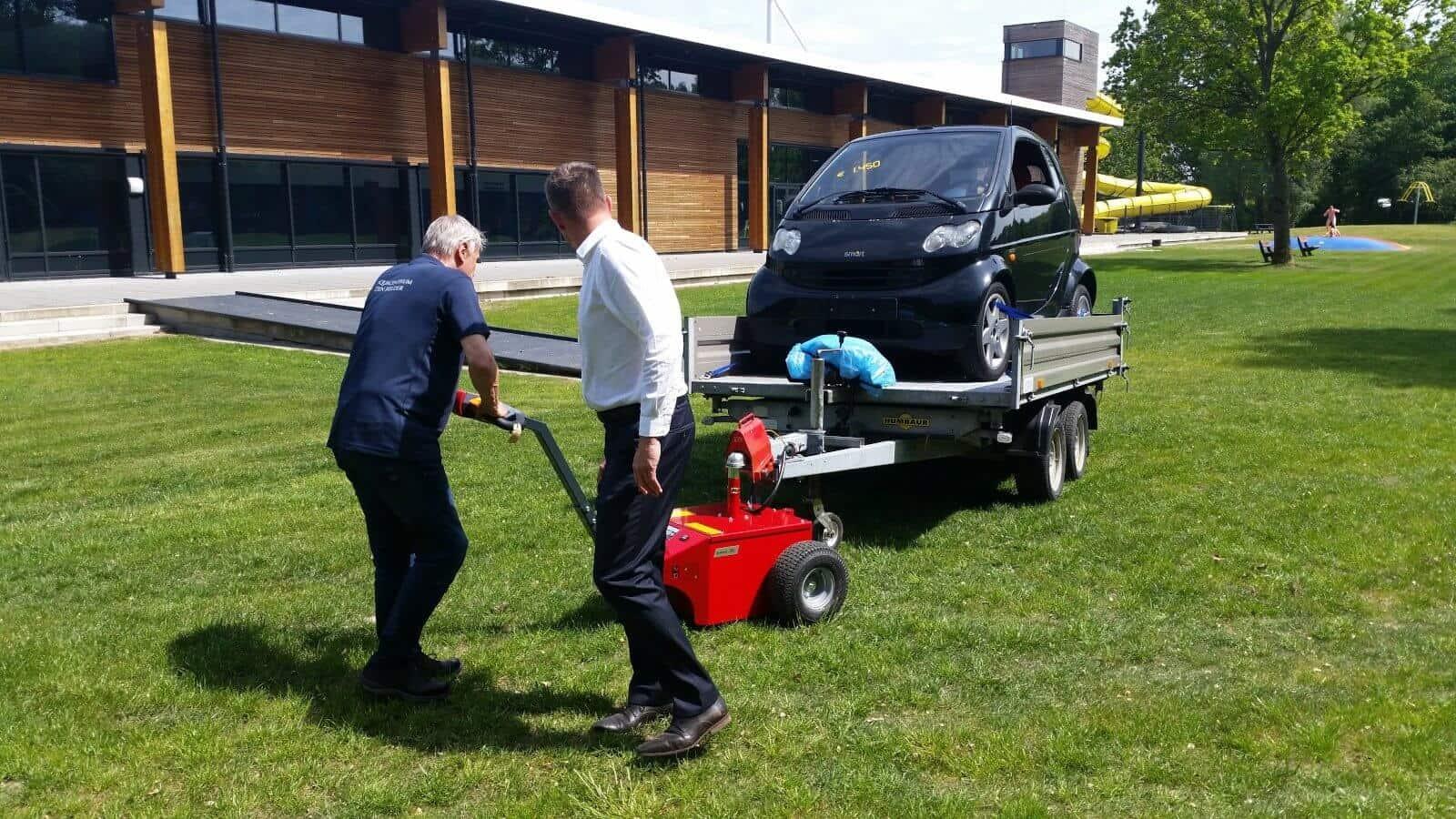 Xerowaste.ca | Remolque o remolcador V-Move XL en movimiento con un vehículo sobre una superficie de césped
