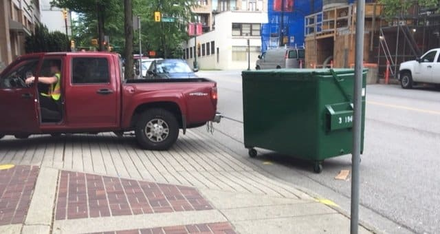 Xerowaste | Dumpster bin being moved by a 3rd party service with a pickup truck. Cheaper and better alternative is a V-move dumpster mover or waste bin tug.
